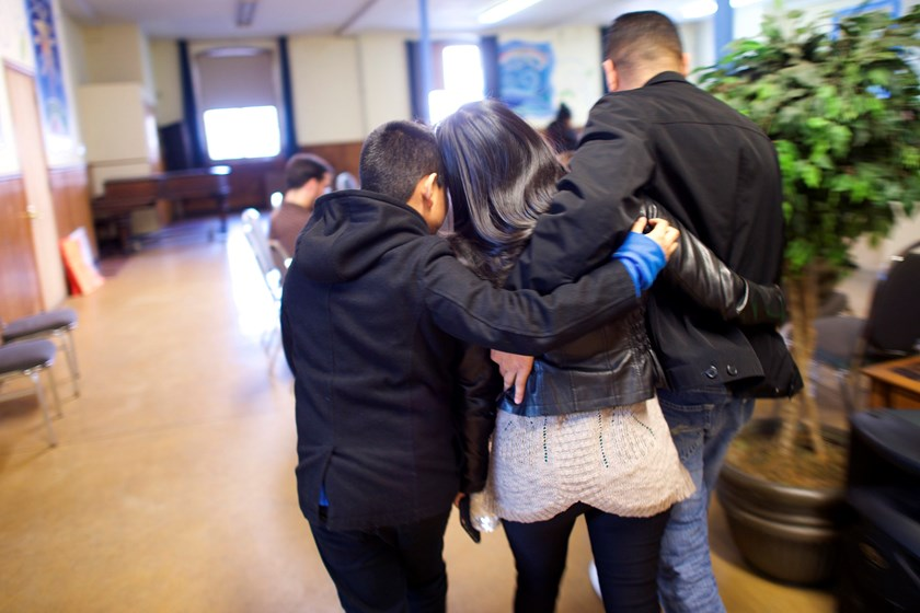 Angela Navarro, an undocumented Honduran-born immigrant with a deportation order, embraces her husband and son after moving into West Kensington Ministry Church with her family, in Philadelphia, Pennsylvania November 18, 2014. Photo credit: Reuters