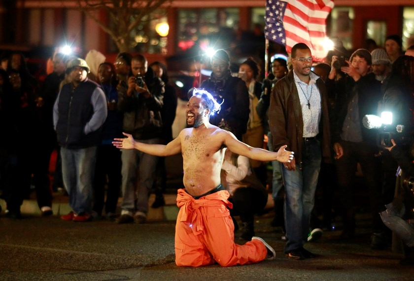A protestor shouts at police as he blocks traffic before being arrested outside the Ferguson Police Station in Ferguson, Missouri November 29, 2014. Photo credit: Reuters