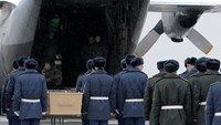 Participants surround a coffin during a farewell ceremony as some of the remains of the victims of Malaysia Airlines flight MH17 are loaded onto a transport plane before it flies to the Netherlands, at Kharkiv airport November 28, 2014. Photo credit: Reut