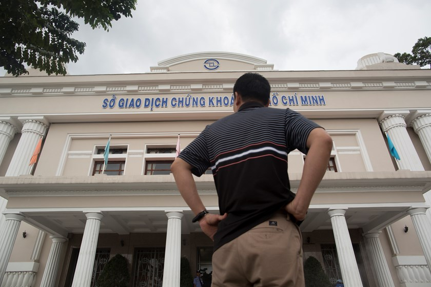 A man stands outside the Ho Chi Minh Stock Exchange (HOSE) in Ho Chi Minh City. International investors will have to wait at least 10 months for Vietnam to ease curbs on foreign shareholders after a 2013 proposal to increase ownership limits was shelved.