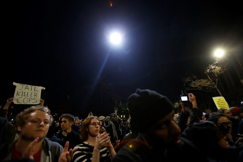 A helicopter flies overhead as protesters march against the New York City grand jury decision to not indict a police officer in the death of Eric Garner in Berkeley, California December 7, 2014. Photo credit: Reuters