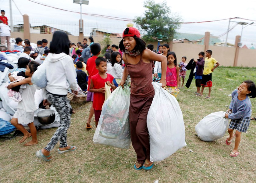 Residents carry sacks of donated clothes at an evacuation center for the coastal community to take shelter from Typhoon Hagupit, in Manila December 8, 2014. Photo credit: Reuters
