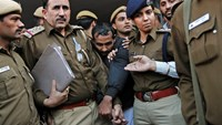 Policemen escort driver Shiv Kumar Yadav (C in black jacket) who is accused of a rape outside a court in New Delhi December 8, 2014. Photo credit: Reuters