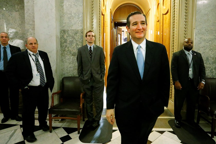 U.S. Senator Ted Cruz (R-TX) (2nd R) smiles as he departs the Senate floor after it passed at $1.1 trillion spending bill following a long series of votes, many on procedural matters or to confirm members of the Obama administration, at the U.S. Capitol i