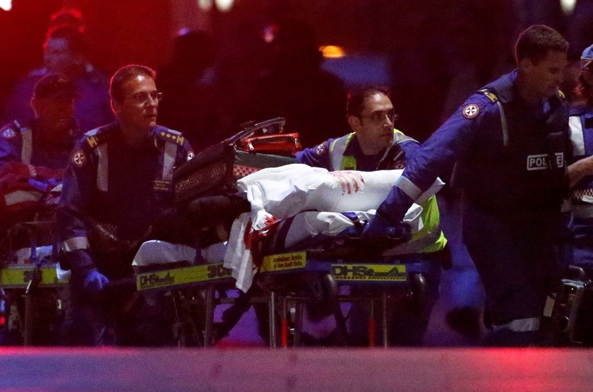 Paramedics remove a person, with bloodstains on the blankets covering the person, on a stretcher from the Lindt cafe, where hostages were being held, at Martin Place in central Sydney December 16, 2014. Photo credit: Reuters