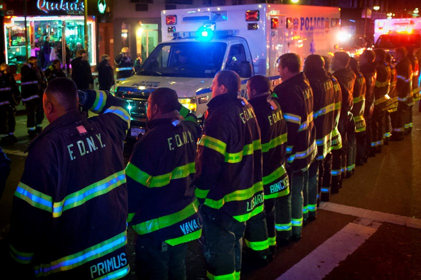 An ambulance carrying one of the two New York Police officers who were shot dead passes by a New York Fire Department honor guard along Broadway in the Brooklyn borough of New York, December 20, 2014. Photo credit: Reuters
