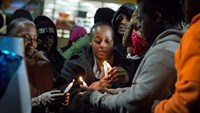 Toni Martin-Green, mother of Antonio Martin, an armed man fatally shot by police late on Tuesday, lights a candle during a vigil for her son in Berkeley, Missouri, December 24, 2014. Photo credit: Reuters
