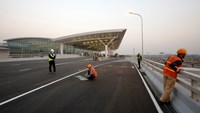 Workers paint on traffic lanes at the new terminal two wing at Noi Bai international airport in Hanoi December 20, 2014. Photo credit: Reuters