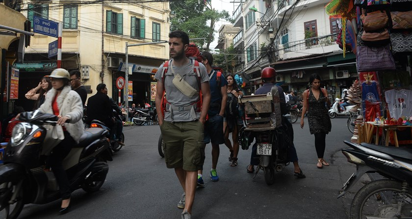 Foreign tourists walk in the ancient quarter of Hanoi on November 13, 2014. The charming old streets of Hanoi are among the main attractions for tourists in Northern Vietnam's Red River region. Photo credit: AFP