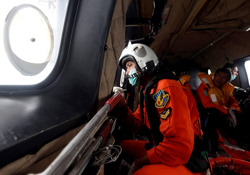 An Indonesian Air Force crew member looks out the windows of a Super Puma helicopter during a search and rescue operation for AirAsia flight QZ8501, over Kumai Bay, south of Pangkalan Bun, Central Kalimantan January 4, 2015. Photo credit: Reuters