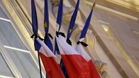 French flags are tied with black tissue at the Elysee Palace in a sign of mourning in Paris January 8, 2015. Photo credit: Reuters