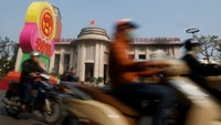 Motorists ride past the State Bank of Vietnam's building in Hanoi December 23, 2014. Photo credit: Reuters