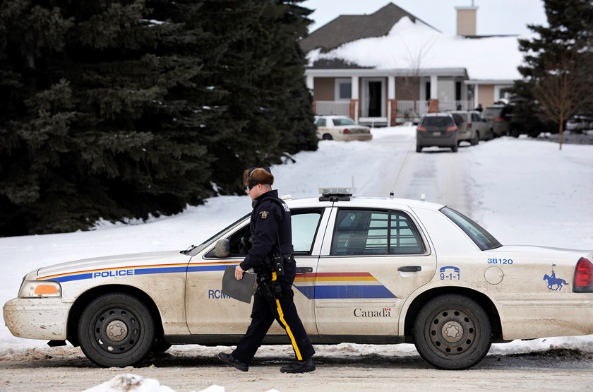 A Royal Canadian Mounted Police (RCMP) officer secures the perimeter of a home where a suspect who is reported to have shot two RCMP officers at the Apex Casino ended his escape effort, near St. Albert, Alberta, January 17, 2015. Photo credit: Reuters