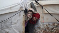 Internally displaced girls look out from their tent inside Al-Karameh refugee camp beside the Syrian-Turkish border in Northern Idlib countryside January 10, 2015. Photo credit: Reuters