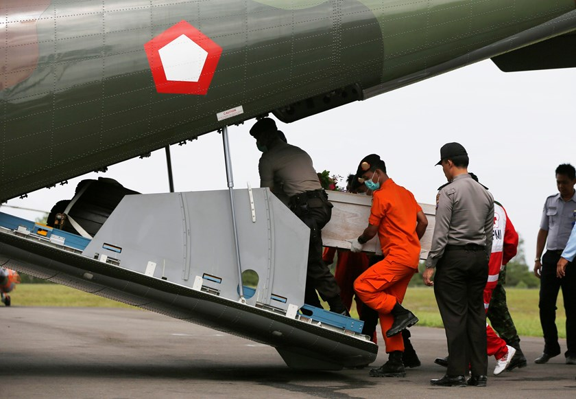 Indonesian policemen and rescue members carry a coffin of a passenger, who was onboard AirAsia Flight QZ8501, into a CN2950 airplane belonging to the Indonesian airforce at the Iskandar airbase in Pangkalan Bun, January 19, 2015. Photo credit: Reuters