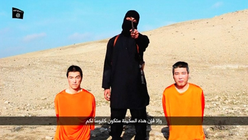 A masked person holding a knife speaks as he stands in between two kneeling men in this still image taken from an online video released by the militant Islamic State group on January 20, 2015. Photo credit: Reuters