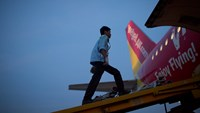 An employee walks up a ramp toward a VietJet Air aircraft, operated by VietJet Aviation Joint Stock Co., at Noi Bai International Airport in Hanoi. Photo credit: Bloomberg