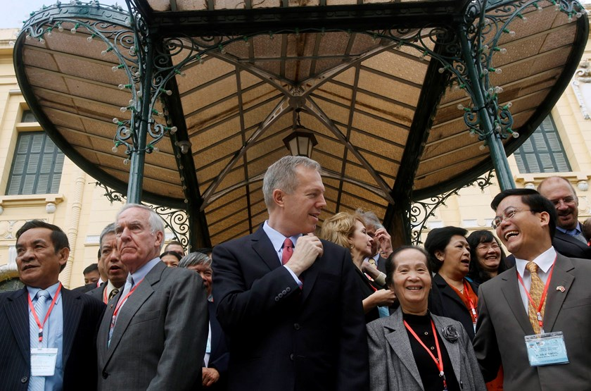 US Ambassador to Vietnam Ted Osius (C) chats with Vietnam's Deputy Minister of Foreign Affairs Ha Kim Ngoc (R) while posing for photos with attendees at a bilateral conference at the Government Guesthouse in Hanoi January 26, 2015. Photo credit: Reuters