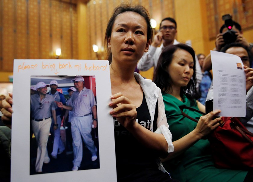 Kelly (last name not given), 29, the wife of a passenger aboard the missing Malaysia Airlines Flight MH370, holds a picture of her husband walking with Malaysia's Prime Minister Najib Razak, at a news conference in Putrajaya January 29, 2015. Photo credit