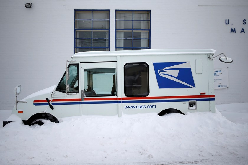 A U.S. Postal service delivery truck sits covered in snow outside the post office in Manhasset, New York January 27, 2015. Photo credit: Reuters