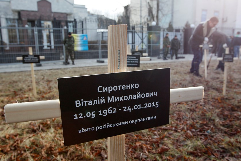 A cross with the name of a victim who was killed in the shelling of the government-held port of Mariupol by pro-Russian rebels on January 24, is pictured during a protest against Russia's actions in Donetsk region in front of Russian embassy in Kiev, Febr