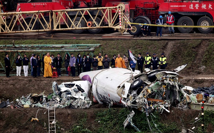 Relatives of the victims pray during a Buddhist ritual near the wreckage of TransAsia Airways plane Flight GE235 after it crash landed into a river, in New Taipei City, February 5, 2015. Photo credit: Reuters