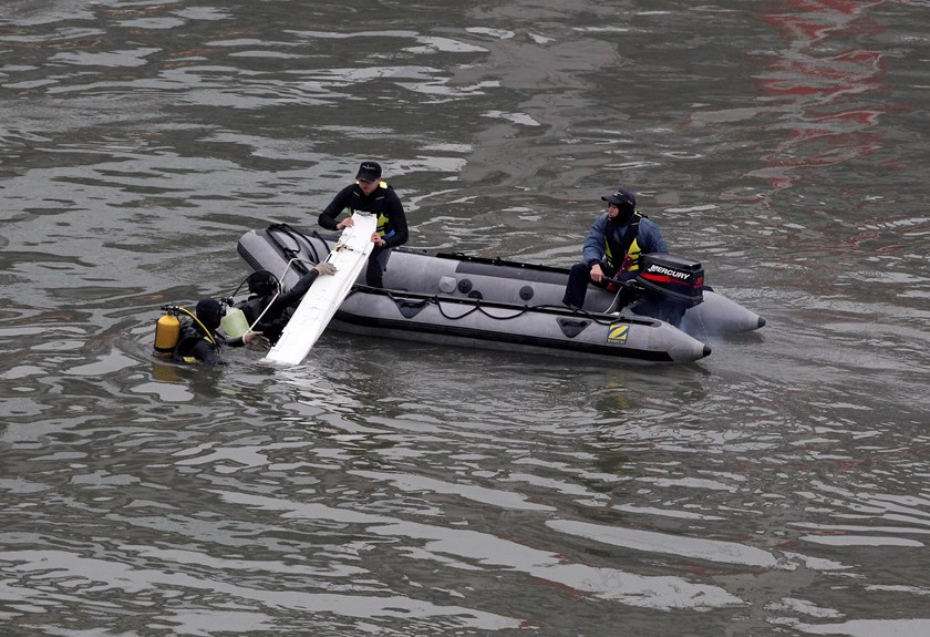 Rescue personnel retrieve an airplane part from the waters near the wreckage of TransAsia Airways plane Flight GE235 after it crash landed into a river, in New Taipei City February 5, 2015. Photo credit: Reuters