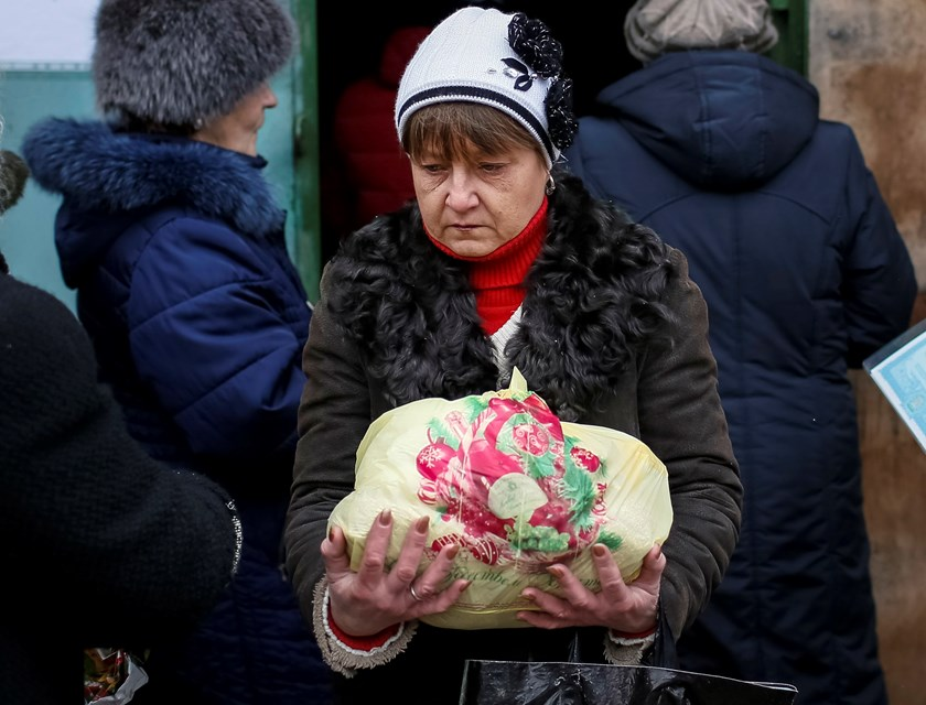 A refugee from eastern Ukraine carries a bag of food as others stand in a queue to receive aid donated to a volunteer center in Slaviansk February 7, 2015. Photo credit: Reuters