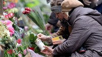 Two women light a candle at a memorial for the victims of the deadly attacks in front of the synagogue in Krystalgade in Copenhagen, February 15, 2015. Photo credit: Reuters