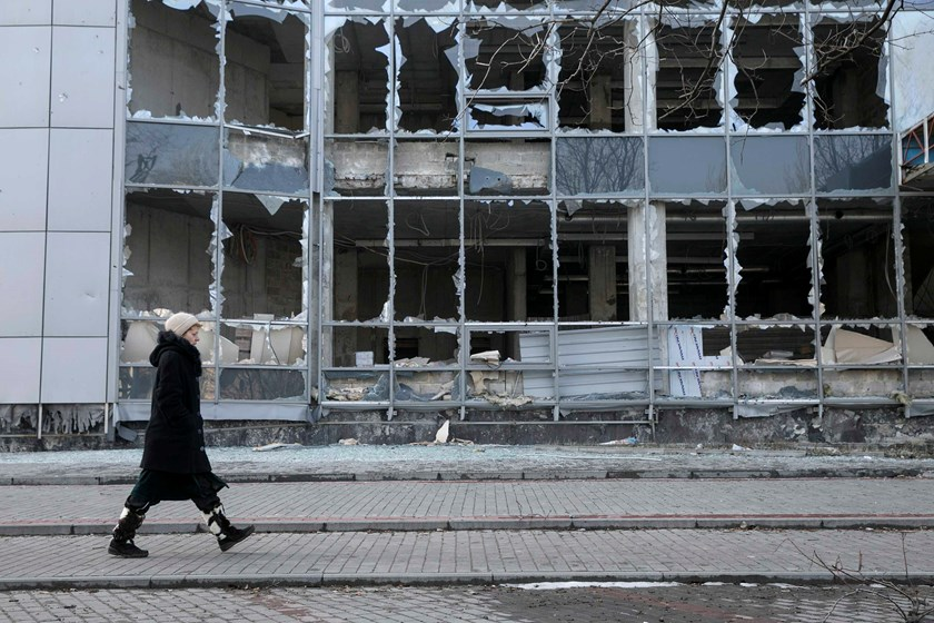 A woman walks by a building, which was damaged by shelling last September, in Donetsk, February 15, 2015. Photo credit: Reuters