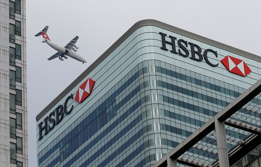 A Swiss International aircraft flies past the HSBC headquarters building in the Canary Wharf financial district in east London February 15, 2015. Photo credit: Reuters