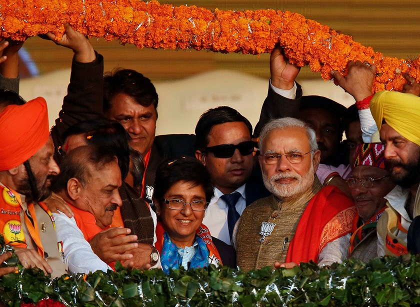 Supporters of India's ruling Bharatiya Janata Party (BJP) present a garland to Prime Minister Narendra Modi (front 3rd R) and BJP's chief ministerial candidate for Delhi Kiran Bedi (C, wearing blue scarf) during a campaign rally ahead of state assembly el