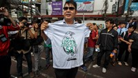 Thai pro-democracy protester Akkarakit Noonchan (C) holds up his symbolic T-shirt near Victory Monument in Bangkok February 22, 2015. Photo credit: Reuters