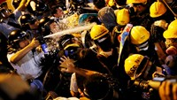 Police use pepper spray during clashes with pro-democracy protesters close to the chief executive office in Hong Kong in this November 30, 2014 file photo. Photo credit: Reuters
