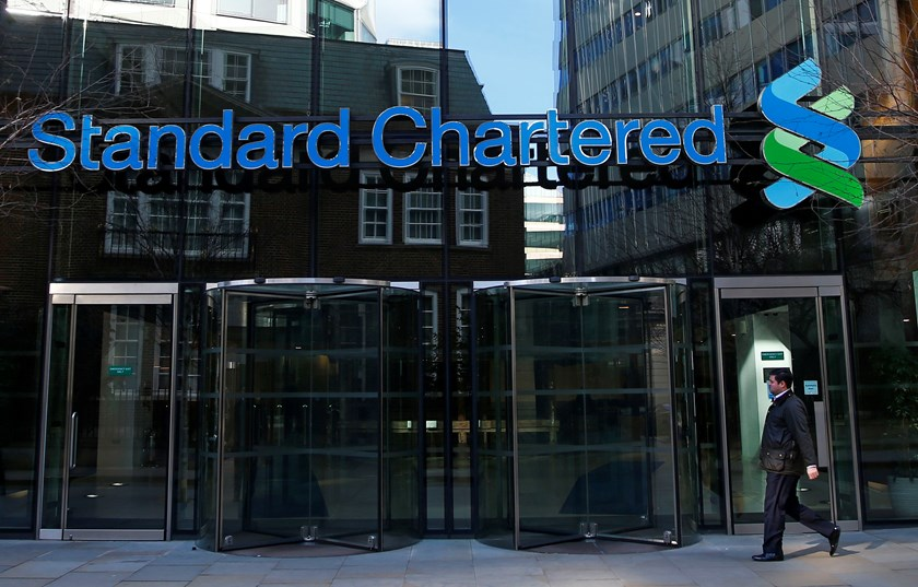 A man walks past the head office of Standard Chartered bank in the City of London February 27, 2015. Photo credit: Reuters