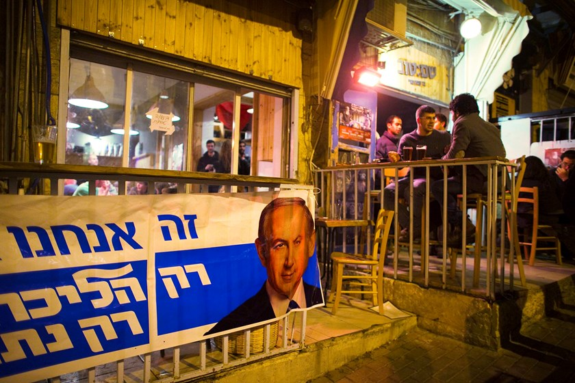 A Likud campaign poster depicting Israel's Prime Minister Benjamin Netanyahu hangs outside a pub in Jerusalem February 24, 2015. Photo credit: Reuters