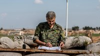 A Kurdish People's Protection Units (YPG) fighter inspects documents left behind by Islamic State fighters at an abandoned barricade in Tel Hamis in Hasaka countryside, after YPG took control of the area, March 1, 2015. Photo credit: Reuters