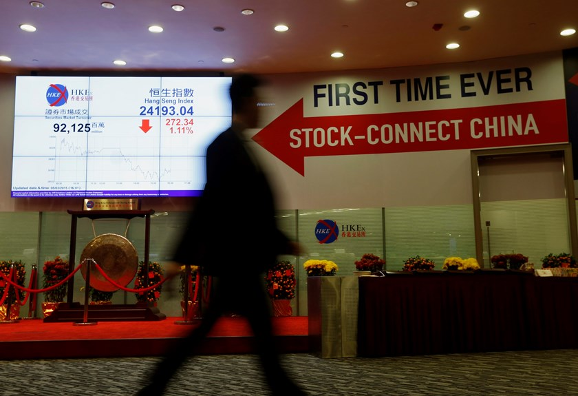 "A man walks past a panel displaying the closing blue chip Hang Seng Index and a banner on ""Shanghai-Hong Kong Stock Connect"" inside the Hong Kong Exchange in Hong Kong March 5, 2015.  Photo credit: Reuters"