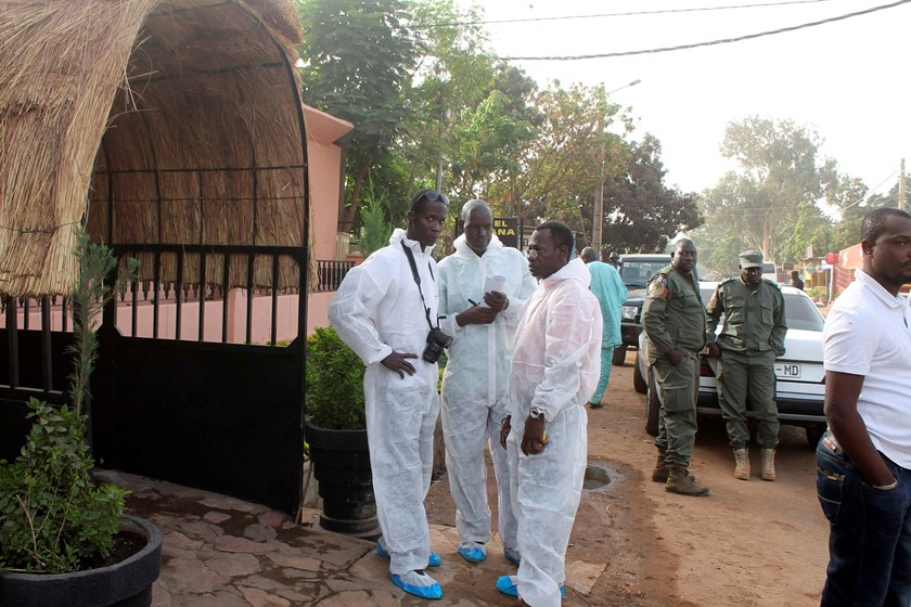 Health officials stand outside La Terrasse restaurant where militants killed five people, including a French citizen and a Belgian citizen, in a gun attack in Bamako March 7, 2015. Photo credit: Reuters