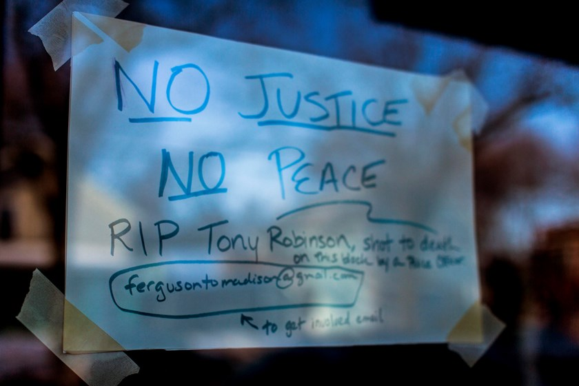 A sign in a store window pays tribute to a 19-year-old black man killed by police, at the 1100 block of Williamson Street in Madison, Wisconsin March 7, 2015. Photo credit: Reuters