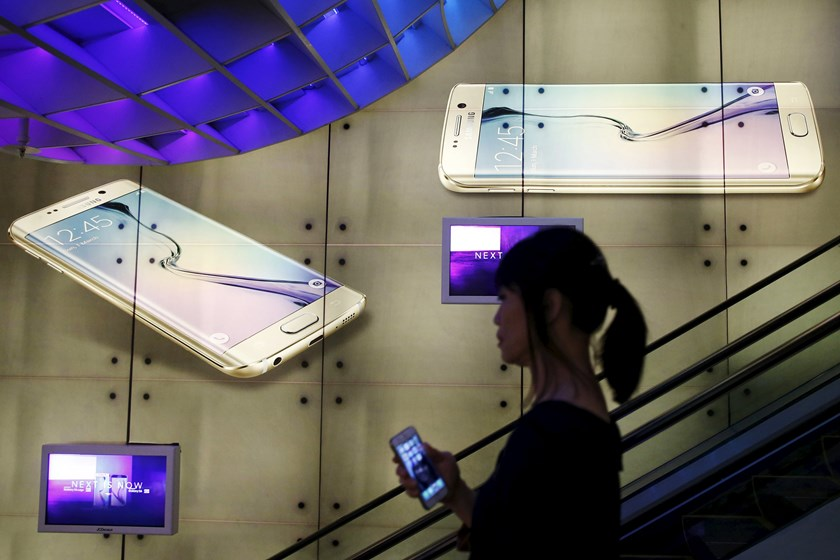 A woman holding an Apple iPhone passes a Samsung Galaxy S6 advertisement at a mall in Singapore April 24, 2015. Photo: Reuters