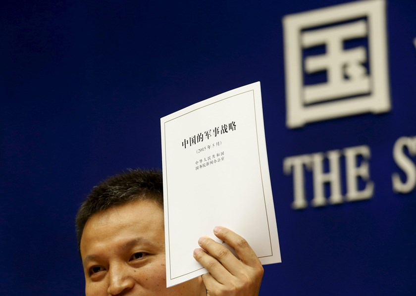 Spokesperson of Chinese Ministry of National Defense Senior Colonel Yang Yujun holds a copy of the annual white paper on China's military strategy during a news conference in Beijing, China, May 26, 2015. Photo: Reuters