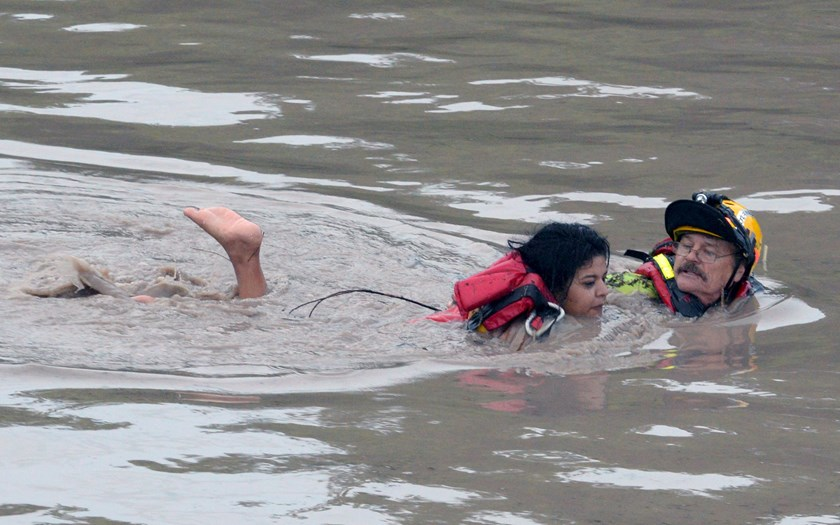 San Marcos Firefighter Jay Horton (R) rescues a woman from in flood waters in San Marcos, Texas May 24, 2015. Photo: Reuters