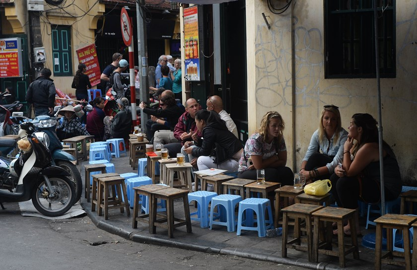 Foreign tourists enjoy food and drinks at small odienpen-air restaurants in the ancient quarter of Hanoi. The charming old streets of Hanoi are among the main attractions for tourists in Northern Vietnam's Red River region. Photo: AFP