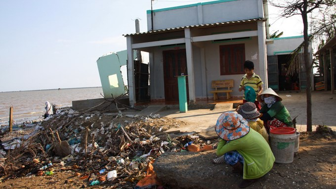 Locals sit in front of the house of Nguyen Thi Trang's mother, which is next to her house that was swept away by sea erosion. Photo credit: Tuoi Tre