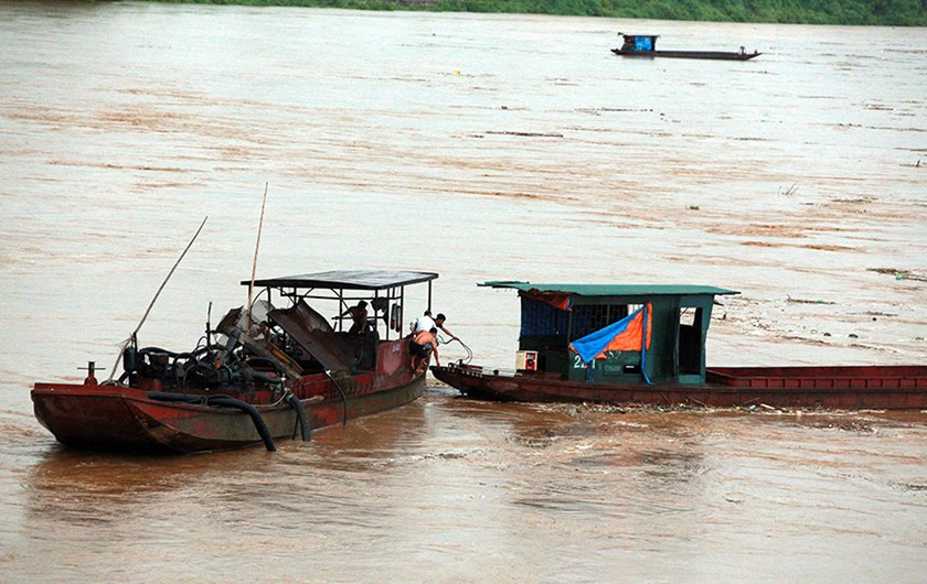Fishermen in Lao Cai Province pull a boat swept far away from the Red River banks due to floodwaters July 14. Photo: Ngoc Bang