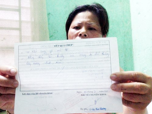Trang shows a hospital's document which read that her nose and cheekbone were broken. Photo: Nguyen Tu