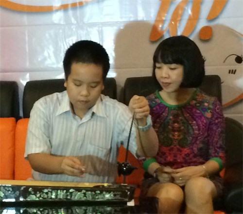 Do Nhat Nam plays dan bau (monochord) as his mother looks on at his talkshow in Ho Chi Minh City on August 3. Photo: Ngoc Bi