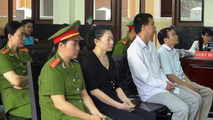 A file photo shows Tran Thi That (2nd, L) closing her eyes during a court judging her and two other accused in March 2014. Photo credit: Tuoi Tre
