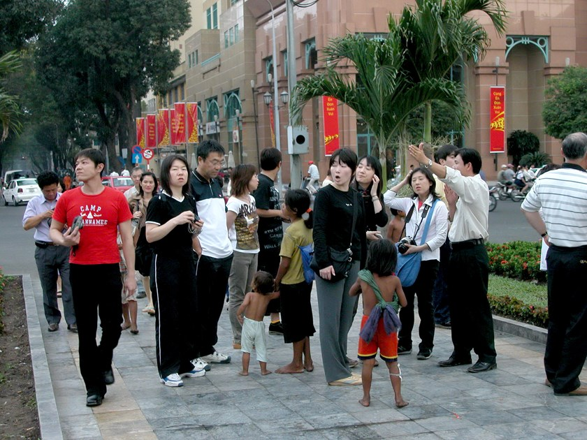 A group of tourists on a street in Ho Chi Minh City. Photo: DDM